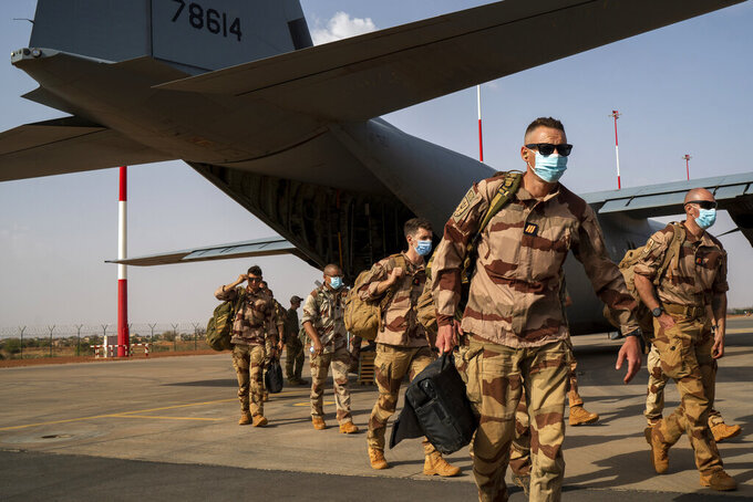 French Barkhane soldiers arriving from Gao, Mali, disembark from a US Air Force C130 cargo plane at Niamey, Niger base Wednesday June 9, 2021, before transferring back to their Bases in France. French President Emmanuel Macron announced at a press conference Thursday June 10, 2021 That operation Barkhane would end and be replaced by support for local partners and counter terrorism. (AP Photo/Jerome Delay)