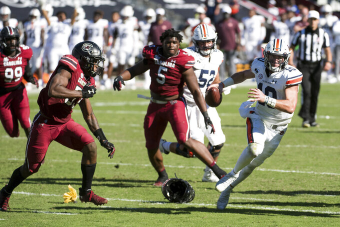 Auburn quarterback Bo Nix (10) scrambles from the pocket against South Carolina linebacker Ernest Jones (53) and Keir Thomas (5) during the second half of an NCAA college football game Saturday, Oct. 17, 2020, in Columbia, S.C. South Carolina defeated Auburn 30-22. (AP Photo/Sean Rayford)