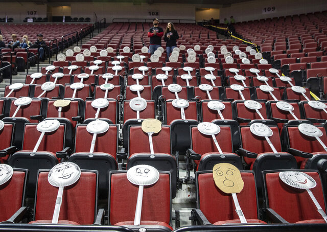 The Auburn fan section got creative by placing paper plate faces on the seats during the Class 1C boys high school basketball tournament championship game against Ogallala at Pinnacle Bank Arena, Saturday, March 14, 2020, in Lincoln, Neb. Crowds were limited to staff and immediate family due to concerns over the coronavirus. For most people, the new coronavirus causes only mild or moderate symptoms. For some it can cause more severe illness, especially in older adults and people with existing health problems. (Chris Machian/Omaha World-Herald via AP)