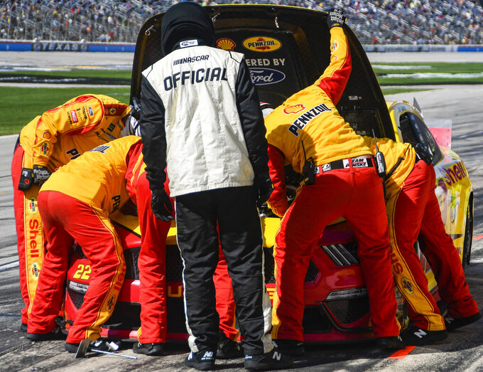 Driver Joey Logano's pit crew inspect under the hood of his car during a NASCAR Cup auto race at Texas Motor Speedway, Sunday, March 31, 2019, in Fort Worth, Texas. (AP Photo/Randy Holt)