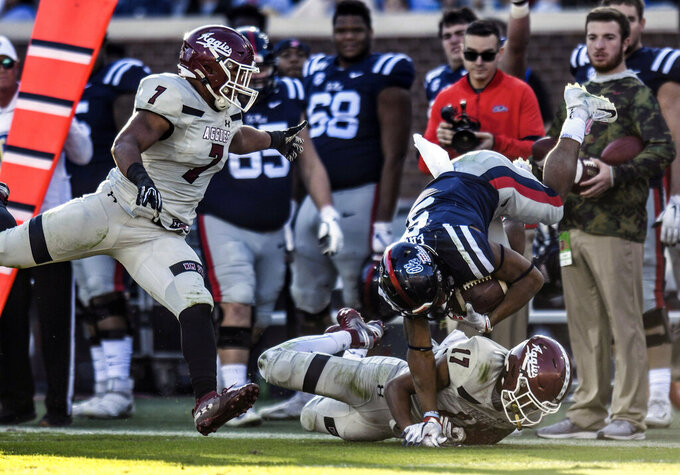 Mississippi running back Jerrion Ealy (9) is tackled by New Mexico State defensive back Jason Simmons Jr. (17) as New Mexico State linebacker Javahn Fergurson (7) pursues during an NCAA college football game in Oxford, Miss., Saturday, Nov. 9, 2019. (Bruce Newman/The Oxford Eagle via AP)