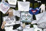 FILE - In this May 28, 2020, file photo, Tributes to lost love ones adorn a fence outside Brooklyn's Green-Wood Cemetery where many victims of COVID-19 are buried in New York. The U.S. death toll from COVID-19 has topped 600,000, even as the vaccination drive has drastically slashed daily cases and deaths and allowed the country to emerge from the gloom. (AP Photo/Mark Lennihan, File)
