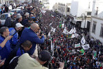 People take snapshot of a gathering against the government and the upcoming presidential elections in Algiers, Algeria, Friday, Dec. 6, 2019. Thousands of protesters took to the streets of the capital after Friday prayers. (AP Photo/Toufik Doudou)