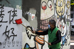 A worker cleans up a vandalized wall Monday, Dec. 9, 2019, in Hong Kong. Hundreds of thousands of demonstrators crammed into Hong Kong's streets on Sunday, their chants echoing off high-rises, in a mass show of support for the protest movement entering its seventh month. (AP Photo/Kiichiro Sato)