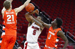 Syracuse's Kadary Richmond (3) knocks the ball from North Carolina State's Thomas Allen (5) as Syracuse's Marek Dolezaj (21) also defends during the first half of an NCAA college basketball game, Tuesday, Feb. 9, 2021 in Raleigh, N.C. (Ethan Hyman/The News & Observer via AP, Pool)