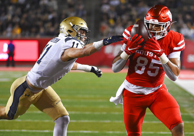 Houston tight end Christian Trahan (85) catches a pass as Navy safety Evan Fochtman defends during the first half of an NCAA college football game, Saturday, Nov. 30, 2019, in Houston. (AP Photo/Eric Christian Smith)