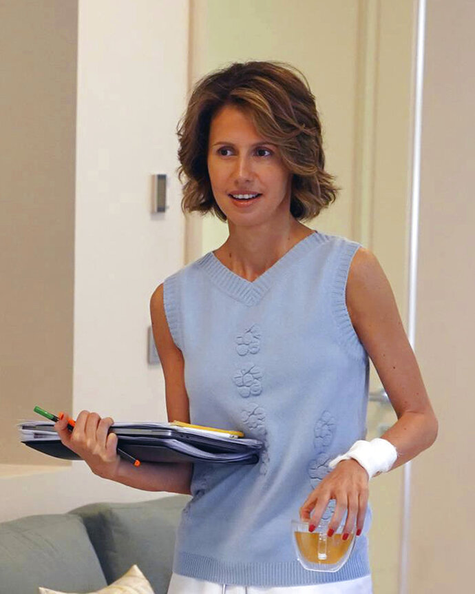 This photo posted Wednesday, Aug 8, 2018 on the official Facebook page of the Syrian Presidency, shows the first lady Asma Assad, wife of Syrian President Bashar Assad, carrying her laptop in one hand and a cup in her left bandaged arm, in Syria. Syria's presidency said that the first lady has begun treatment for breast cancer. The statement said the