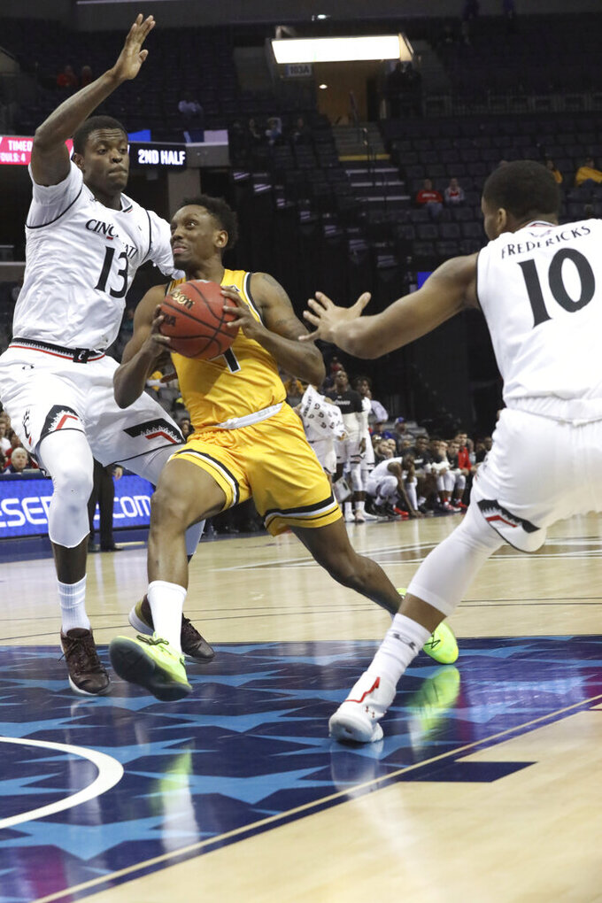 Wichita State's Samajae Haynes-Jones drives the ball past Cincinnati player Tre Scott defends in the second half of an NCAA college basketball game at the American Athletic Conference tournament Saturday, March 16, 2019, in Memphis, Tenn. (AP Photo/Troy Glasgow)