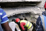 Rescue workers attempt to rescue a person from a collapsed building in Tasia Embakasi, an east neighbourhood of Nairobi, Kenya on Friday Dec. 6, 2019.  A six-story building collapsed in Kenya's capital on Friday, officials said, with people feared to be trapped in the debris. Police say people have been rescued by residents using their bare hands. (AP Photo/Khalil Senosi)