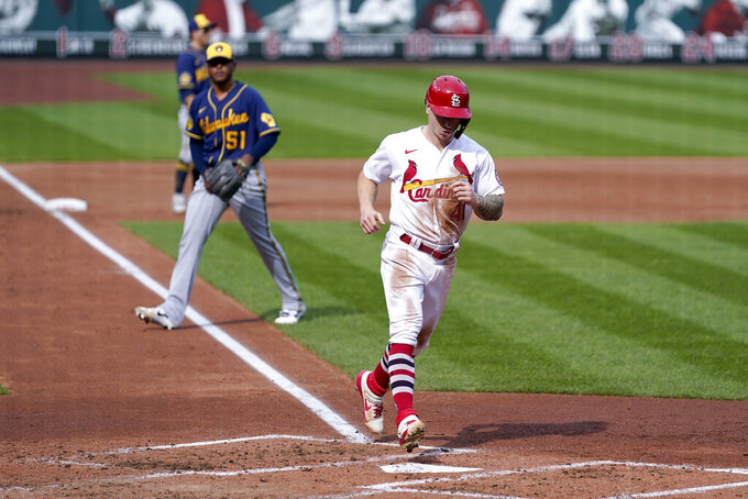 St. Louis Cardinals' Tyler O'Neill, right, scores as Milwaukee Brewers relief pitcher Freddy Peralta (51) watches during the third inning of a baseball game Sunday, Sept. 27, 2020, in St. Louis. (AP Photo/Jeff Roberson)