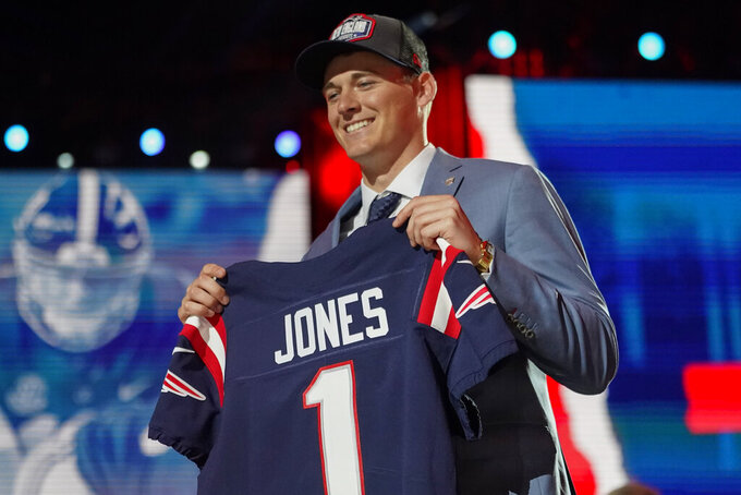 Alabama quarterback Mac Jones holds a team jersey after he was by the New England Patriots during the first round of the NFL football draft, Thursday April 29, 2021, in Cleveland. (AP Photo/Tony Dejak)