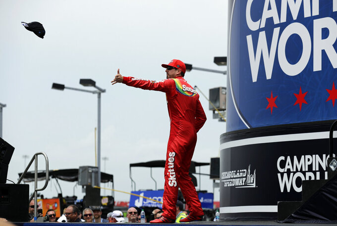 Kyle Busch throws a cap to the crowd during driver introductions before a NASCAR Cup Series auto race at Chicagoland Speedway in Joliet, Ill., Sunday, June 30, 2019. (AP Photo/Nam Y. Huh)