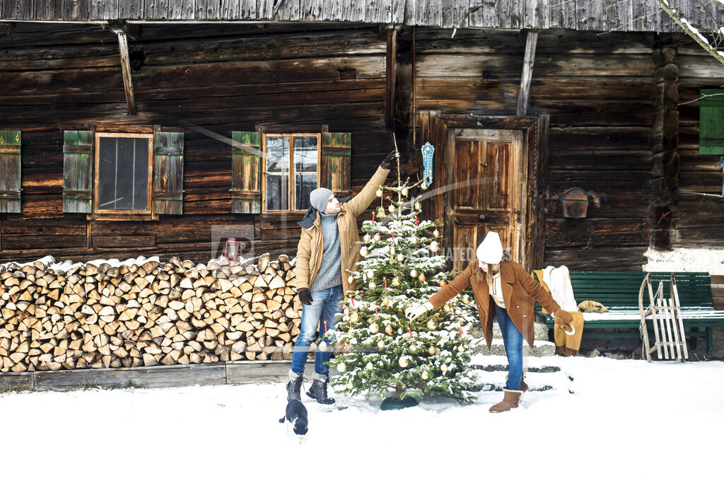 Young couple decorating Christmas tree during winter