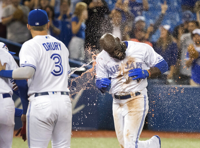 Toronto Blue Jays' Anthony Alford gets a sports drink shower as he arrives at home plate after hitting a walk-off home run to end the ballgame in the 15th inning against the Baltimore Orioles, Monday, Sept. 23, 2019, in Toronto. Toronto won 11-10. (Fred Thornhill/The Canadian Press via AP)