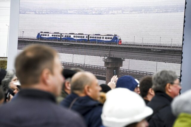 People watch a giant TV screen with Russian President Vladimir Putin, inside, riding a train across a bridge linking Russia and the Crimean peninsula in Taman, Russia, Monday, Dec. 23, 2019. Putin on Monday inaugurated a railway bridge to Crimea, the longest in Europe, which is intended to facilitate links with Crimea, which Russia annexed from Ukraine in 2014. (AP Photo)