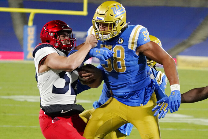 Arizona place holder Jacob Meeker-Hackett, left, is pushed out of bounds by UCLA defensive lineman Datona Jackson (58) after a botched field goal-attempt during the second half of an NCAA college football game Saturday, Nov. 28, 2020, in Pasadena, Calif. (AP Photo/Marcio Jose Sanchez)