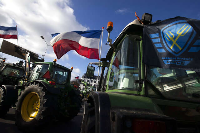 The Farmers Defense Force flag, right, and Dutch flags, fly in the wind on an intersection blocked by tractors in The Hague, Netherlands, Wednesday, Feb. 19, 2020. Dutch farmers, some driving tractors, poured into The Hague on Wednesday to protest government moves to rein in carbon and nitrogen emissions to better fight climate change. (AP Photo/Peter Dejong)