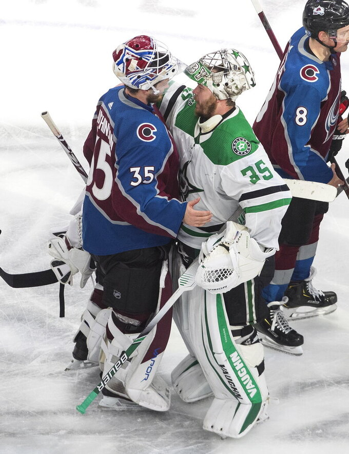 Colorado Avalanche goalie Michael Hutchinson (35) and Dallas Stars goalie Anton Khudobin (35) hug after Dallas won during overtime NHL Western Conference Stanley Cup playoff game action in Edmonton, Alberta, Friday, Sept. 4, 2020. (Jason Franson/The Canadian Press via AP)