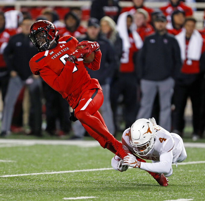Texas Tech's T.J. Vasher (9) is tackled by Texas' Anthony Cook (4) during the second half of an NCAA college football game Saturday, Nov. 10, 2018, in Lubbock, Texas. (AP Photo/Brad Tollefson)