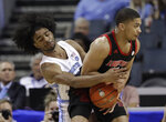 North Carolina's Coby White, left, reaches across to strip the ball from Louisville's Christen Cunningham, right, during the first half of an NCAA college basketball game in the Atlantic Coast Conference tournament in Charlotte, N.C., Thursday, March 14, 2019. (AP Photo/Chuck Burton)