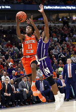 Illinois guard Ayo Dosunmu, left, drives to the basket against Northwestern guard Anthony Gaines during the second half of an NCAA college basketball game in the first round of the Big Ten Conference tournament in Chicago, Wednesday, March 13, 2019. Illinois won 74-69 in overtime. (AP Photo/Nam Y. Huh)