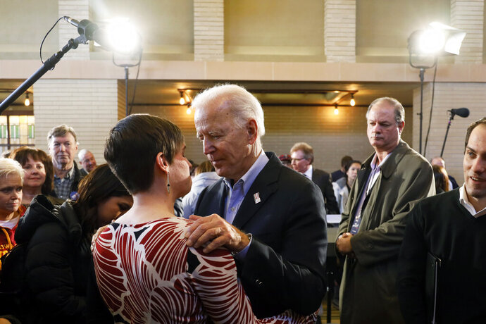 Democratic presidential candidate former Vice President Joe Biden talks with Theresa Hanley, of Mason City, Iowa, left, during a bus tour stop, Tuesday, Dec. 3, 2019, in Mason City, Iowa. (AP Photo/Charlie Neibergall)