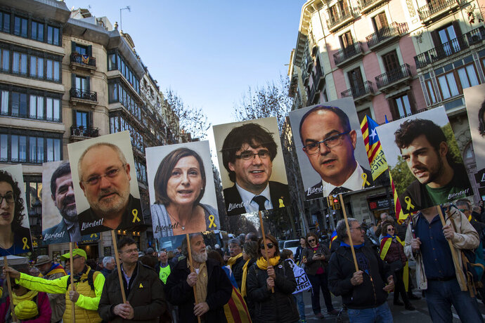 FILE - In this Saturday, Feb. 16, 2019 file photo, pro independence demonstrators hold photos of imprisoned and exiled pro-independence political leaders, during a demonstration in Barcelona, Spain. A dozen politicians and activists on trial for their failed bid in 2017 to carve out an independent Catalan republic in northeastern Spain will deliver their final statements Wednesday June 12, 2019, as four months of hearings draw to an end. (AP Photo/Emilio Morenatti, File)