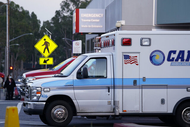 Ambulances are parked outside an emergency room entrance at Long Beach Medical Center, Tuesday, Jan. 5, 2021, in Long Beach, Calif. (AP Photo/Ashley Landis)