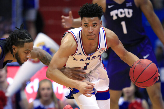 Kansas guard Devon Dotson (1) steals the ball from TCU guard PJ Fuller, left, during the first half of an NCAA college basketball game in Lawrence, Kan., Wednesday, March 4, 2020. (AP Photo/Orlin Wagner)