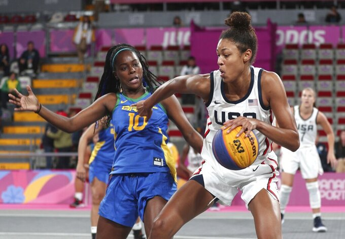 """FILE - In this July 29, 2019, file photo, Olivia Nelson, right, of the United States, drives around Evelyn Mariano, of Brazil, during the women's basketball 3x3 semifinal match at the Pan American Games in Lima, Peru. The Olympics website calls 3x3 basketball """"exciting, urban and innovative."""" It was added to the program for Tokyo to lure a younger audience and get more countries involved in one of the core sports of the Olympic Games. (AP Photo/Martin Mejia, File)"""