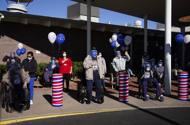 Residents and staff listen to the national anthem during a socially-distanced Veterans Day ceremony at the Southern Nevada State Veterans Home, Wednesday, Nov. 11, 2020, in Boulder City, Nev. The special outdoor ceremony was held with face coverings and distancing as a precaution against the coronavirus. (AP Photo/John Locher)