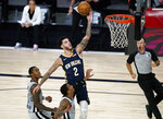 New Orleans Pelicans guard Lonzo Ball (2) makes a shot as he gets between San Antonio Spurs' Lonnie Walker IV, left, and guard Dejounte Murray, center, during the second half of an NBA basketball game, Sunday, Aug. 9, 2020, in Lake Buena Vista, Fla. (AP Photo/Ashley Landis, Pool)