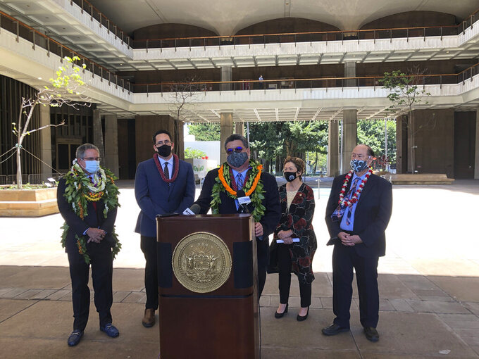 Hawaii Senate President Ron Kouchi speaks at a podium at the state Capitol in Honolulu on Thursday, April 29, 2021, flanked from left to right by Sens. Kalani English, Jarrett Keohokalole, Michelle Kidani and Brian Taniguchi. Hawaii's lawmakers are wrapping up a legislative session marked by a generous influx of federal aid that helped the islands weather the shock of the coronavirus pandemic. (AP Photo/Audrey McAvoy)