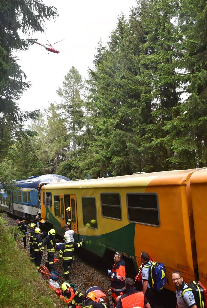 This photo  provided by HZSKVK, shows emergency services at the scene after two trains collided, near the village of Pernink, Czech Republic, Tuesday July 7, 2020. Officials say two passenger trains collided head-on in western Czech Republic, killing at least two people on board and injuring about 20. The Czech Rail Safety Inspectorate says the collision took place after 3 p.m. (1300 GMT) Tuesday between the stations Nove Hamry and Pernink near the German border (HZSKVK via AP)