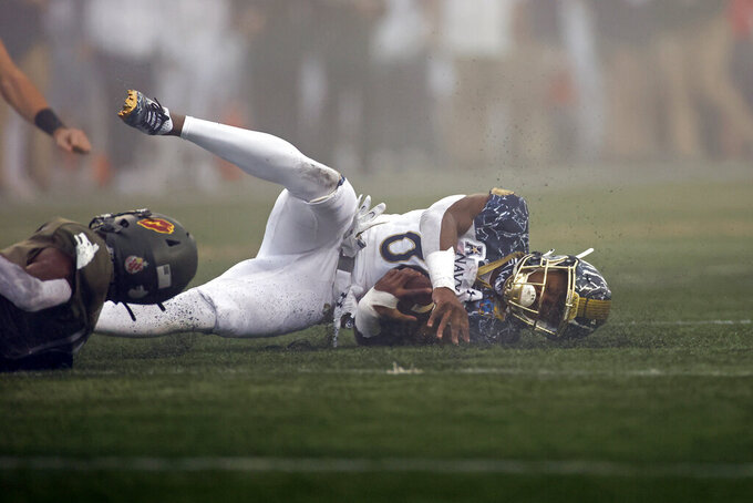 Navy wide receiver Mark Walker is tackled during the first half of an NCAA college football game against Army on Saturday, Dec. 12, 2020, in West Point, N.Y. (AP Photo/Adam Hunger)