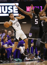 San Antonio Spurs guard Bryn Forbes, left, passes under the arm of Sacramento Kings guard De'Aaron Fox during the first quarter of an NBA basketball game Monday, Feb. 4, 2019, in Sacramento, Calif.(AP Photo/Rich Pedroncelli)