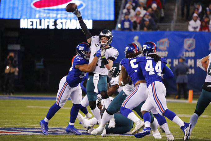 Philadelphia Eagles quarterback Carson Wentz (11) passes in front of New York Giants linebacker Oshane Ximines (53) in the first half of an NFL football game, Sunday, Dec. 29, 2019, in East Rutherford, N.J. (AP Photo/Seth Wenig)