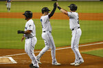 Miami Marlins' Brian Anderson, center, celebrates with Garrett Cooper, right, and Harold Ramirez after Anderson hit a home run scoring the two during the first inning a baseball game against the San Diego Padres, Tuesday, July 16, 2019, in Miami. (AP Photo/Wilfredo Lee)
