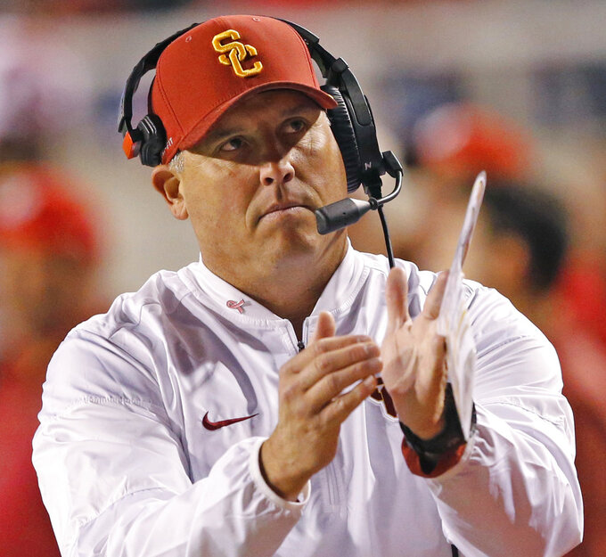 FILE - In this Saturday, Oct. 20, 2018, file photo, Southern California head coach Clay Helton calls for a timeout in the first half of an NCAA college football game against Utah, in Salt Lake City. In a decision announced Tuesday, Nov. 27, 2018, offensive coordinator Tee Martin, defensive line coach Kenechi Udeze and defensive backs coach Ronnie Bradford are not being retained by Helton following the Trojans' first losing season in 18 years. (AP Photo/Rick Bowmer, File)