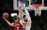 Boston Celtics center Aron Baynes, right,blocks the path of Miami Heat guard Goran Dragic (7) during the first quarter of an NBA basketball game in Boston, Monday, April 1, 2019. (AP Photo/Charles Krupa)