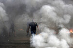 An anti-government protester walks between burning tires that were set fire to block a road during a protest against government's plans to impose new taxes in Beirut, Lebanon, Friday, Oct. 18, 2019. Demonstrators in Lebanon are blocking major roads across the country in a second day of protests against proposed new taxes, which come amid a severe economic crisis. (AP Photo/Hassan Ammar)