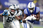 FILE - In this Dec. 22, 2019, file photo, Carolina Panthers' Luke Kuechly (59) charges Indianapolis Colts running back Marlon Mack (25) during the first half of an NFL football game in Indianapolis. The Panthers will look to upgrade their defense in the NFL draft after losing nine starters from last year's unit, including five-time All-Pro linebacker Kuechly. (AP Photo/Michael Conroy, File)