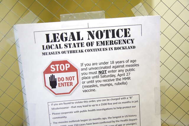 FILE - In this Wednesday, March 27, 2019 file photo, a sign at the Rockland County Health Department in Pomona, N.Y., explains the local state of emergency regarding a measles outbreak. There were nearly 1,300 case of measles in the U.S. through November 2019 - the largest number in 27 years. There were no deaths but about 120 people ended up in the hospital. (AP Photo/Seth Wenig)