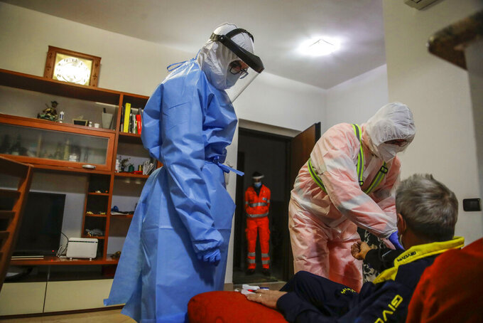 Medical staffer Ruggero Gariboldi, right, measures oxygen level in the blood of a suspected Covid patient inside his home during a shift with the emergency White Cross in Monza, Italy, Friday, Nov. 20, 2020.  The city of Monza north of Milan is best known for its Formula 1 racetrack. In 2020, it has been the ambulance service that has been doing most of the racing. Over three days that an Associated Press photographer traveled on night calls with an ambulance service, the Monza-Brianza province of some 875,000 bordering Milan added 2,500 new cases, part of Italy's new epicenter in the Lombardy region. (AP Photo/Luca Bruno)
