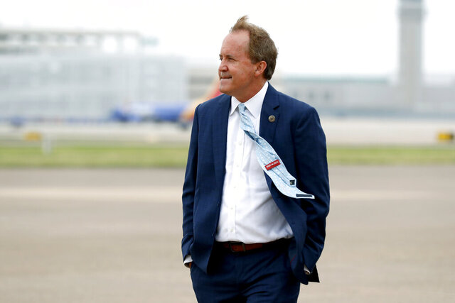 FILE - In this June 28, 2020 file photo, Texas' Attorney General Ken Paxton waits on the flight line for the arrival of Vice President Mike Pence at Love Field in Dallas. The mass exodus of Paxton's top staff over accusations of bribery against their former boss has left the Republicans seeking $43 million in public funds to replace some of them with outside lawyers to lead a high-profile antitrust lawsuit against Google. (AP Photo/Tony Gutierrez, File)