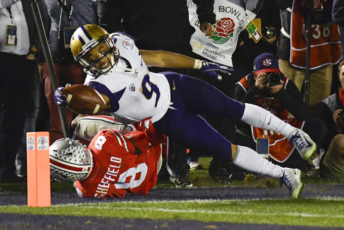 Washington running back Myles Gaskin, top, scores past Ohio State cornerback Kendall Sheffield during the second half of the Rose Bowl NCAA college football game Tuesday, Jan. 1, 2019, in Pasadena, Calif. Ohio State won 28-23. (AP Photo/Mark J. Terrill)