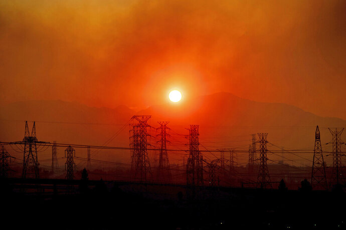 FILE - In this Oct. 11, 2019, file photo, smoke from a wildfire called the Saddle Ridge Fire hangs above power lines as the sun rises in Newhall, Calif. Fire danger remains high as dry, warm winds blow through Southern California. The National Weather Service says gusts on Sunday, Oct. 20, could top 60 mph (97 kph) in some parts of Los Angeles, Ventura and Santa Barbara counties. Southern California Edison says it's monitoring conditions to determine whether preventive power shut-offs will be needed. (AP Photo/Noah Berger, File)