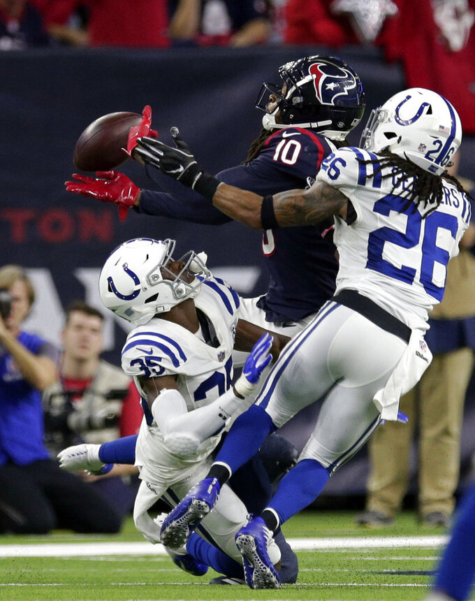 Indianapolis Colts cornerback Pierre Desir (35) and strong safety Clayton Geathers (26) break up a pass intended for Houston Texans wide receiver DeAndre Hopkins (10) during the second half of an NFL wild card playoff football game, Saturday, Jan. 5, 2019, in Houston. (AP Photo/Michael Wyke)