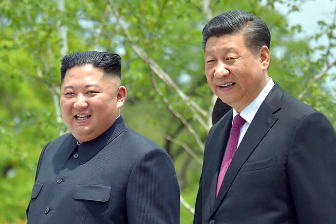 "FILE - In this June 21, 2019, file photo provided by the North Korean government, North Korean leader Kim Jong Un, left, and Chinese President Xi Jinping stroll in the premises of Kumsusan guest house in Pyongyang, North Korea. Kim in a message to Xi called for stronger ""unity and cooperation"" between the countries in the face of challenges posed by ""hostile forces,"" the North's state media and Tuesday, March 23, 2021. (Korean Central News Agency/Korea News Service via AP, File)"