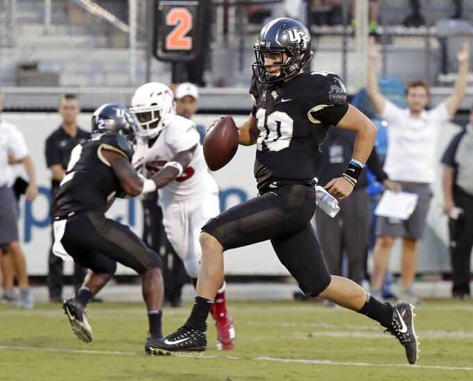 FILE - In this Sept. 21, 2018, file photo, Central Florida quarterback McKenzie Milton (10) runs for a 12-yard touchdown against Florida Atlantic during the first half of an NCAA college football game, in Orlando, Fla. He accounted for six TDs each of the last two games, passing for seven and running for five. UCF plays SMU on Saturday. (AP Photo/John Raoux, File)